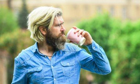 Photo pour Café de troisième vague. Un homme barbu qui boit du café. L'homme boit du café fond déconcentré. Emportez le café. Dose de caféine. Bonne humeur. Une tasse en papier. Café et restaurant. Mesures de sécurité. Coupe personnelle. - image libre de droit