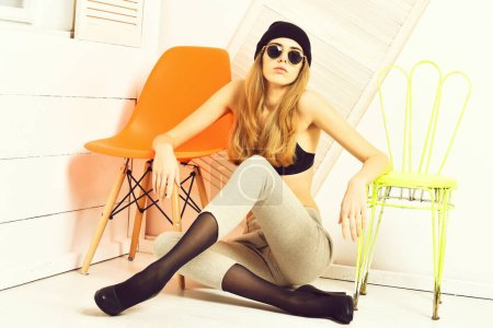 Photo for Pretty woman or sexy cute girl with long blonde hair and adorable face in sunglasses, bra, hat, shoes and pants, sits at orange and light green chair on white studio background - Royalty Free Image