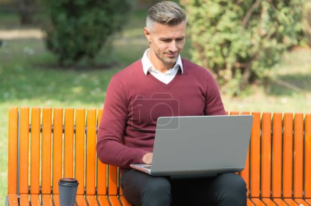 Photo pour Agile business. good morning. mature handsome man work on laptop outdoor. well groomed man sit on bench with coffee. confident businessman is online. casual business fashion. - image libre de droit