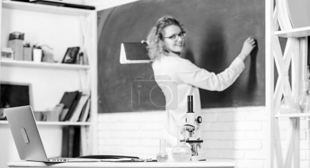 Photo pour Biology laboratory. Microbiology and bioengineering. Microscope ant tubes with chemical liquids on table school biology teacher selective focus. Student writing chalkboard defocused. Biology concept. - image libre de droit