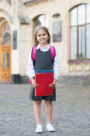 Photo pour Preparing for study. Happy child hold study books outdoors. Back to school supplies. Fashion uniform. Formal dress code. Schoolwear. September 1. Primary education. Private teaching. Home schooling. - image libre de droit