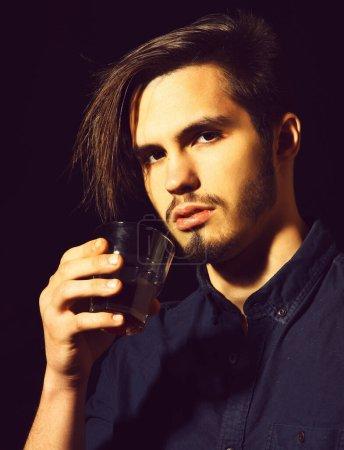 Photo pour Bel homme barbu en chemise bleue avec des cheveux élégants sur le visage sérieux tenant verre de whisky en arrière-plan studio noir - image libre de droit