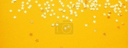 Foto de Las estrellas doradas brillan sobre el fondo de papel amarillo. Vacaciones festivas brillante telón de fondo - Imagen libre de derechos
