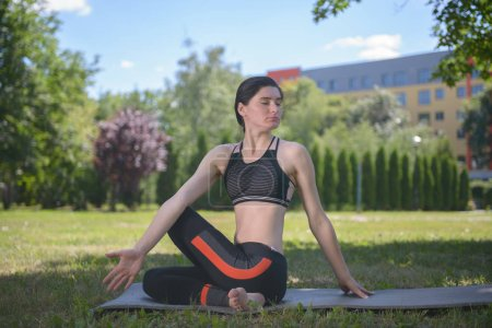 Young Woman Engaging in Yoga Gymnastics in the Park
