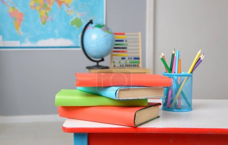 Textbooks and color pencils on the school desk - c...