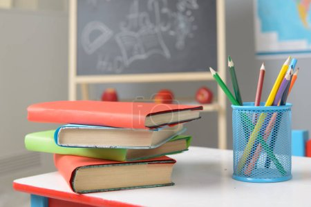 Textbooks and color pencils on the school desk...