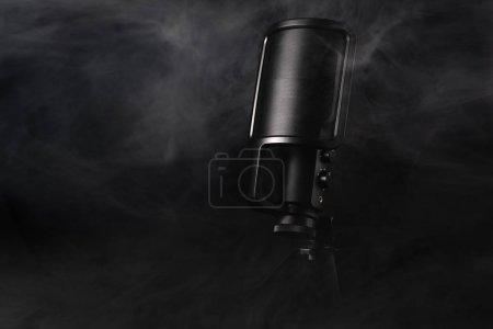 Photo pour Micro noir sur un fond noir avec de la fumée - image libre de droit