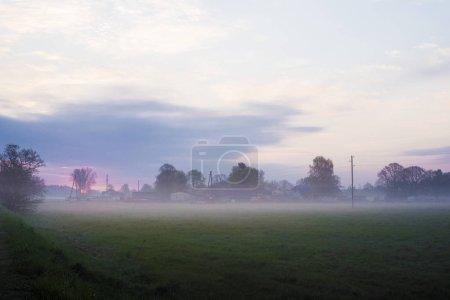 Photo pour Lever de soleil de printemps coloré en Lettonie. Vue sur la campagne verdoyante sous le brouillard matinal - image libre de droit