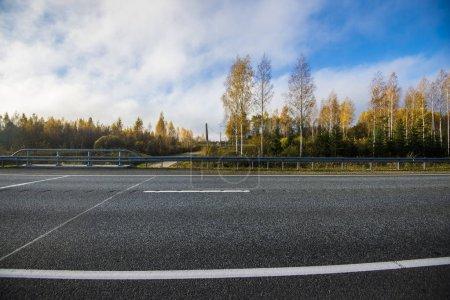 Photo pour Gros plan sur la route de campagne asphaltée en Lettonie par une belle journée d'automne - image libre de droit