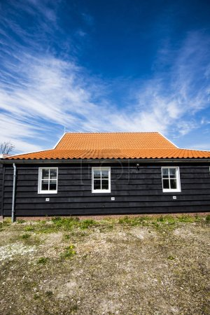 A view of an old wooden house with a red tile roof on a sunny spring day, Holland
