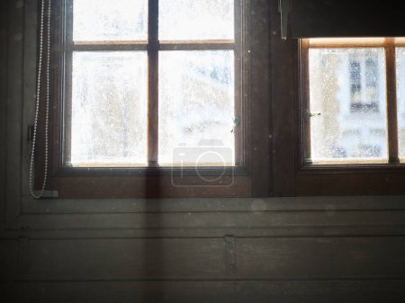 Shot of a dirty window with light coming in and dust visible in the foreground