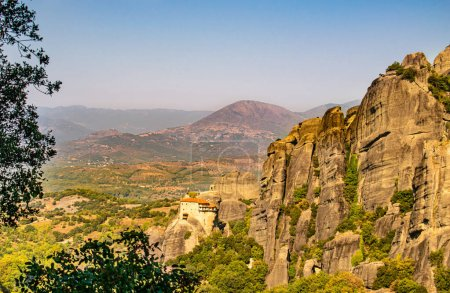 Monastery Meteora Greece. Stunning  panoramic landscape. View of mountains and green forest against epic blue sky with clouds. UNESCO heritage object.
