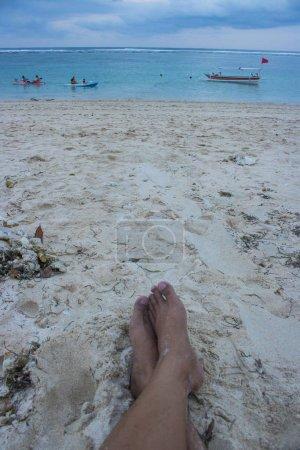 Photo pour Image recadrée de pieds et de morue bière sur la plage de sable - image libre de droit