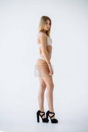 Studio shot of lovely blonde girl in sexy beige lingerie standing on white background