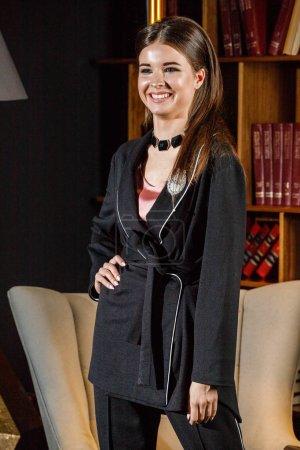Retrato de una hermosa mujer morena con camiseta rosa y traje negro de pie en el interior del hogar con estantería en el fondo