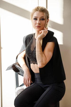 Portrait of beauty blonde woman in black casual clothes sitting on wooden chair in luxury room interior