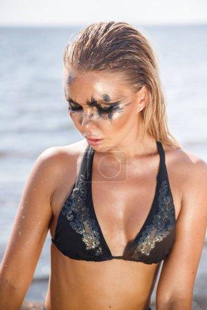 Primer plano retrato de hermosa chica morena mujer en traje de baño oscuro de pie en la playa durante el día