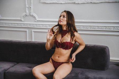 Photo pour Beauté brunette femme en lingerie rouge assis sur le canapé dans des appartements de luxe intérieur - image libre de droit