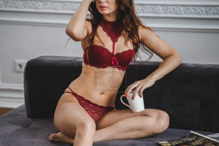 Photo for Beauty brunette woman in red lingerie sitting on sofa at luxury apartments interior - Royalty Free Image