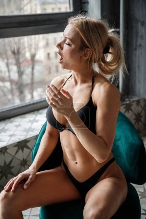 Photo pour Belle blonde fitness posant à l'intérieur de la chambre. Studio photo de modèle sexy dans des appartements de luxe - image libre de droit
