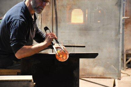Photo pour Souffleur de verre formant, transformant le verre chauffé en un beau cheval de verre décoratif dans une manufacture sur l'île de Murano, Venise, Italie - image libre de droit
