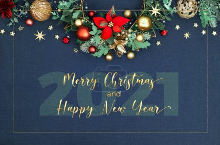 Photo for Merry Christmas and Happy New Year 2021!. Decorative Christmas border, floral garland with eucalyptus, baubles, trinkets and red poinsettia. Red, green, golden Xmas decorations on classic blue linen background. - Royalty Free Image