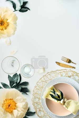 Contemporary table setting with peony flowers and golden utensils on white table. Modern trendy flat lay, top view on table decorated in yellow and green. Pentecost pfingstenrosen design, copy-space.