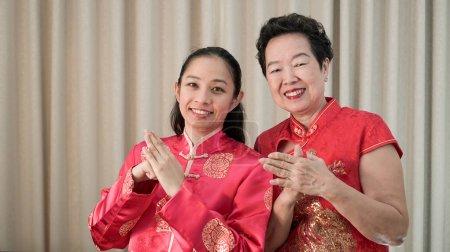 Asiatique mère et fille en droit en Chiense costume rouge pour Nouveau