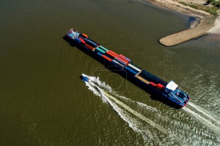 Photo for Rhine - Netherlands, July 14, 2018: aerial view of a merchant ship with a container crossing the river Rhine in a region of the Netherlands - Royalty Free Image