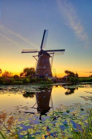 Photo pour Vue sur les moulins à vent traditionnels au coucher du soleil à Kinderdijk, Pays-Bas. Ce système de 19 moulins à vent a été construit vers 1740 et est un site du patrimoine mondial de l'UNESCO . - image libre de droit