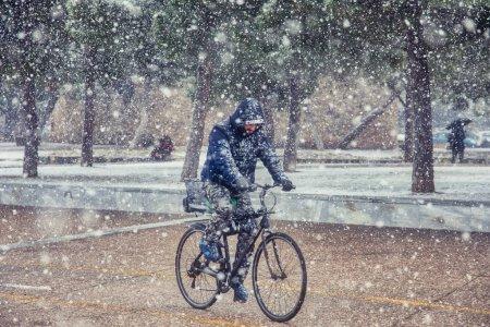 Foto de Salónica, Grecia - 05 de enero de 2019: un ciclista con nieve en el centro de la ciudad en un día de invierno - Imagen libre de derechos
