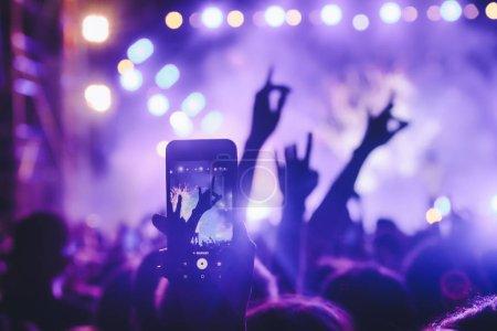 Photo pour Les gens prennent des photos avec téléphone intelligent tactile lors d'un concert public de divertissement musical. concert en direct, festival de musique, jeunesse heureuse, fête de luxe, extérieur paysage. Focus sélectif - image libre de droit