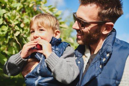 Photo pour Adorable petite fille avec un beau parent millénaire cueillant des fruits biologiques mûrs avec sa famille dans un verger pendant la journée ensoleillée d'automne à la campagne - image libre de droit