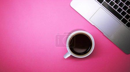 Photo pour Vue supérieure du bureau de lieu de travail, ordinateur portatif avec une tasse de café sur le fond rose lumineux lumineux vide - image libre de droit