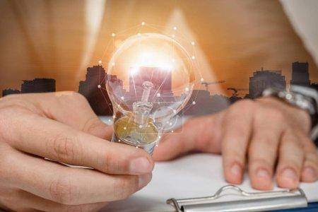 Photo pour Le concept de l'idée d'entreprise. Homme d'affaires tenant une ampoule qui brûle à l'arrière-plan du coucher du soleil urbain. - image libre de droit
