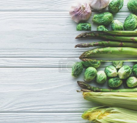 Photo for Collage of ripe green brussels sprouts, asparagus, corn and garlic on white wooden table - Royalty Free Image