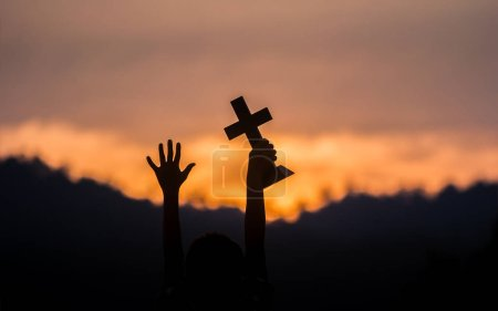 Photo pour Hands off children holding christian cross with light sunset background. - image libre de droit