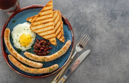 Traditional full English breakfast with fried eggs, sausages and beans on grey background. Top view.