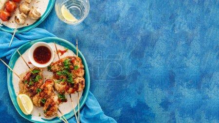 Kebab de poulet sur brochettes avec cerise, champignons et sauce barbecue sur fond bleu. Copyspace. Vue du dessus .