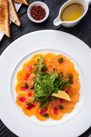 Photo for Tuna and salmon carpaccio with tarragon, capers and lemon - Royalty Free Image