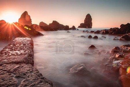Photo pour Lever de soleil dans la mer Méditerranée, vieille pile de ciclopes d'Acitrezza - image libre de droit