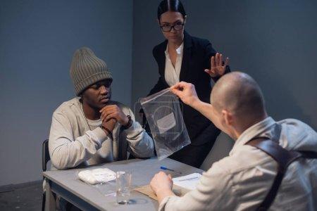Photo pour Un enquêteur expérimenté pendant l'interrogatoire montre le criminel présumé et sa preuve d'avocat du crime commis. - image libre de droit