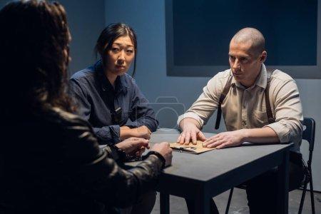 Photo pour Deux policiers un homme et une femme interrogent le présumé contrevenant au poste de police. - image libre de droit