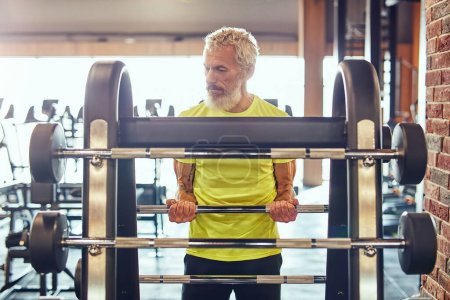 Photo for Sport and bodybuilding concept. Strong mature man in sportswear lifting weighted bar or barbell while working out at gym, exercising with weights. Training, sport, healthy and active lifestyle - Royalty Free Image