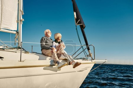 Photo for Enjoying vacation. Happy senior family couple sitting on the side of a sail boat or yacht deck floating in a calm blue sea, hugging and enjoying amazing view. Traveling together, boat trip - Royalty Free Image