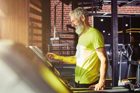 Photo for Cardio workout. Side view of a happy middle aged athletic man in sportswear adjusting speed on a treadmill while exercising in a gym or sport club. Active and healthy lifestyle, training concept - Royalty Free Image