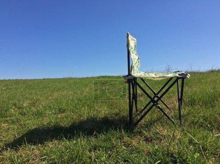 Photo pour Chaise de camping pliante sur fond de ciel et d'herbe - image libre de droit