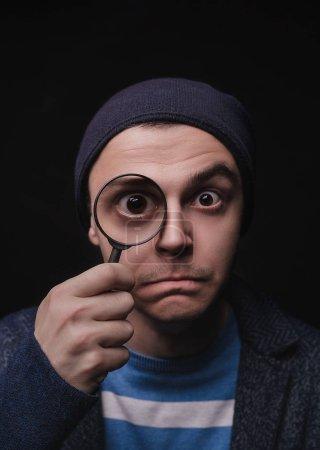 Photo pour Le jeune homme en tenue décontractée avec une loupe. Il cherche des opportunités. Détective privé. Je regarde tout. Explore. Se tourne vers l'avenir - image libre de droit