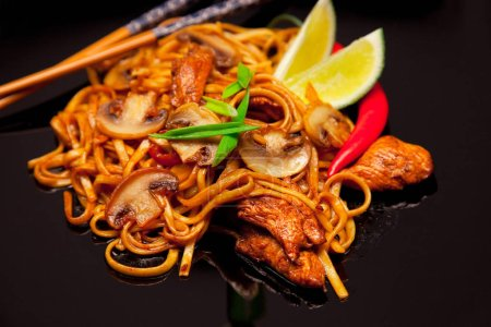 Photo for Thai noodles with spices and chicken on black plate - Royalty Free Image