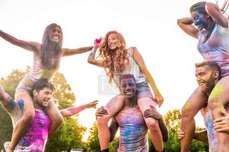 Photo for Group of happy friends playing with holi colors in a park - Young adults having fun at a holi festival, concepts about fun, fun and young generation - Royalty Free Image